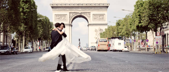 Young newly-weds in front of the Arc de Triomphe